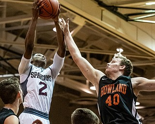 DIANNA OATRIDGE | THE VINDICATOR Boardman's Che Trevena (2) puts up a shot against Howland's Nathan Barrett (40) during the Spartans' 73-42 victory on their home court Friday night.