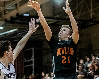 DIANNA OATRIDGE | THE VINDICATOR Howland's Frankie Manios (21) puts up a 3-point shot as Boardman's Shay Eicher (20) defends during the Spartans' 73-42 victory in Boardman on Friday night.