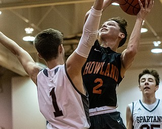 DIANNA OATRIDGE | THE VINDICATOR Howland's Gage Tomko (2) drives to the hoop against Boardman's Tommy Fryda (1) during the Spartans' 73-42 victory in Boardman on Friday night.