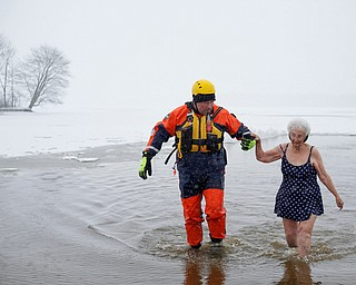 Minnie Wolfe, right, of Niles, participates in the Annual Polar Plunge with assistance from Chris Herlinger, with the Bazetta Fire Department, in Mosquito Lake in Cortland on Saturday. EMILY MATTHEWS   THE VINDICATOR