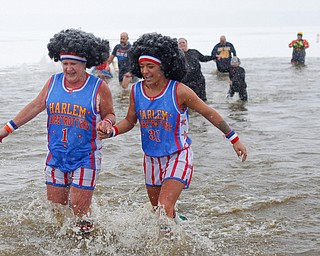 Jodi Omerzo, left, and Rena Ghirardi, both of Cortland, dressed up as the Harlem Globetrotters, participate in the Annual Polar Plunge in Mosquito Lake in Cortland on Saturday. EMILY MATTHEWS   THE VINDICATOR