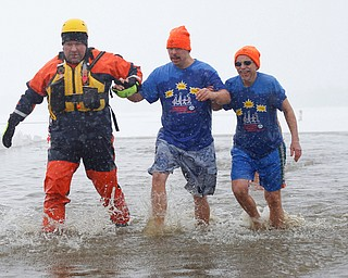 Craig Myers, center, a special olympian from Tampa, Florida, and his uncle Don Strock, right, of Champion, participate in the Annual Polar Plunge with assistance from Chris Herlinger, left, with the Bazetta Fire Department, in Mosquito Lake in Cortland on Saturday. EMILY MATTHEWS   THE VINDICATOR