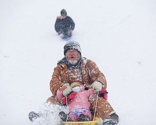 Jason Dean and Mila Cain, 1, of Cornersburg, sled ride at Wick Recreation Area on Saturday afternoon. EMILY MATTHEWS   THE VINDICATOR
