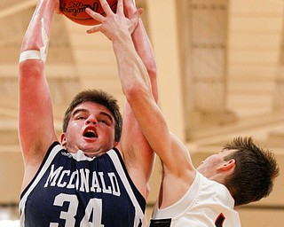 McDonald's Jake Portolese catches a rebound as Mineral Ridge's Austin Governor reaches for the ball during their game at Mineral Ridge on Tuesday night. EMILY MATTHEWS | THE VINDICATOR