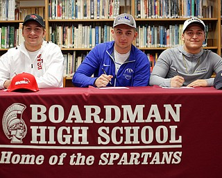 From left, Michael O'Horo, Alex Huzicka, and Kareem Hamdan sign to Saginaw Valley St., Notre Dame College, and Clarion University, respectively, during a signing ceremony in the Boardman High School library on Wednesday. EMILY MATTHEWS | THE VINDICATOR