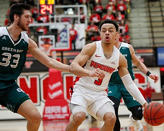 YSU's Darius Quisenberry dribbles the ball while Green Bay's Cody Schwartz tries to block him during their game in Beeghly Center on Saturday night. EMILY MATTHEWS | THE VINDICATOR