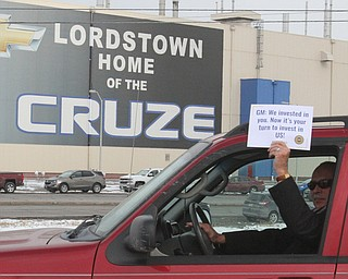 William D. Lewis the vindictor   Greg Hicks, Warren Law Ditecotr holds a sign as he drives by the GM plant 3-6-19.