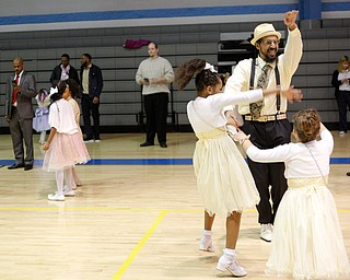 James Bevely dances with his daughters Galaiah Bevely, 10, left, and Ja'lisa Bevely, 7, all of Youngstown, during the Youngstown City School District father-daughter dance at East High School on Friday night. EMILY MATTHEWS   THE VINDICATOR