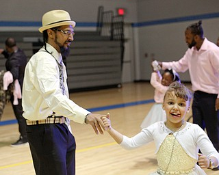 James Bevely dances with his daughter Ja'lisa Bevely, 7, both of Youngstown, during the Youngstown City School District father-daughter dance at East High School on Friday night. EMILY MATTHEWS   THE VINDICATOR