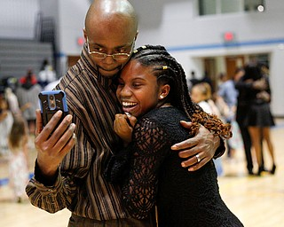 Corey Jolliff takes a photo with his daughter Jaylaysha Jolliff, 14, both of Youngstown, during the Youngstown City School District father-daughter dance at East High School on Friday night. EMILY MATTHEWS   THE VINDICATOR
