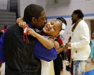 Faybeon Stewart, of Youngstown, kisses his daughter Makyla Stewart, 5, on the cheek during the Youngstown City School District father-daughter dance at East High School on Friday night. EMILY MATTHEWS   THE VINDICATOR