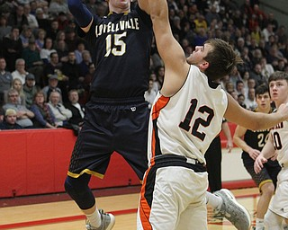 Jake Rotz (15) of Lowellville goes up for a shot while being defended by Shane Eynon (12) of Springfield during Friday nights district championship game at Struthers High School.  Dustin Livesay  |  The Vindicator  3/8/19  Struthers
