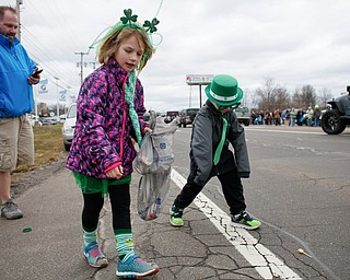 Siblings Nora McMasters, 6, and Liams McMasters, 4, of Austintown, pick up candy as they watch the Mahoning Valley St. Patrick's Day Parade with their dad Ryan McMasters in Boardman on Sunday afternoon. Nora and Liam's younger brother Grant, 2, and mom Heather McMasters were watching from their car. EMILY MATTHEWS | THE VINDICATOR