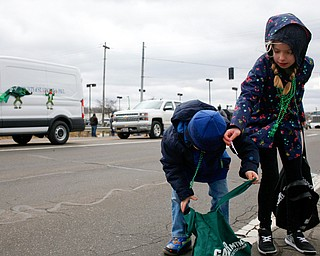 Cousins Preston Harness, 4, left, Lillyana Magielski, 9, of South Range, pick up candy during the Mahoning Valley St. Patrick's Day Parade in Boardman on Sunday afternoon. EMILY MATTHEWS | THE VINDICATOR
