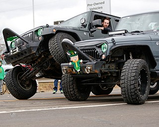 One Jeep driver gets his wheel on top of another driver's wheel as they drive down Market Street during the Mahoning Valley St. Patrick's Day Parade in Boardman on Sunday afternoon. EMILY MATTHEWS | THE VINDICATOR