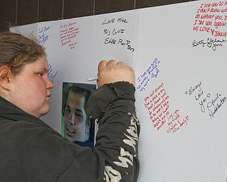 William D. Lewis The Vindicator  Jamie Burke of Struthers signs a poster during a 3-24-19 vigil for a Campbell father and son who were killed ina  car crash.