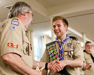 Eagle Scout Colin Russell, of troop 60, shakes hands with Byron Harnishfeger, District Advancement Chairman, as he's recognized with other Eagle Scouts at the Whispering Pines Recognition Dinner in St. James Episcopal Church in Boardman on Sunday. EMILY MATTHEWS   THE VINDICATOR