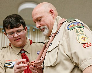 Don Wittman receives his wood badge and his son David Wittman, 17, helps him put a knot on his neckerchief at the Whispering Pines Recognition Dinner in St. James Episcopal Church in Boardman on Sunday. EMILY MATTHEWS   THE VINDICATOR
