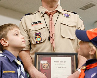 Kevin Miller stands with two of his children, Reece Miller, 9, left, and Willow, 7, after receiving his Wood Badge at the Whispering Pines Recognition Dinner in St. James Episcopal Church in Boardman on Sunday. EMILY MATTHEWS   THE VINDICATOR