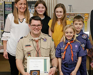 Kevin Miller holds his District Award of Merit as his family, including his wife Julie Miller and children Riley Miller, 14, Whitney Miller, 11, Willow Miller, 7, and Reece Miller, 9, stand around him at the Whispering Pines Recognition Dinner in St. James Episcopal Church in Boardman on Sunday. EMILY MATTHEWS   THE VINDICATOR