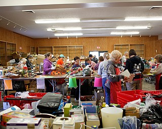 Volunteers get the main room ready for the Angels for Animals garage sale in building 24 at the Canfield Fairgrounds on Tuesday morning. The garage sale will take place Friday through Sunday at the fairgrounds. EMILY MATTHEWS | THE VINDICATOR