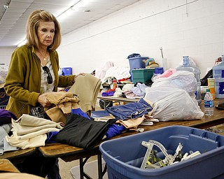 Volunteer Cheryl Pinten, of Boardman, organizes clothes that will be for sale at the Angels for Animals garage sale at the Canfield Fairgrounds on Tuesday morning. The garage sale will take place Friday through Sunday at the fairgrounds. EMILY MATTHEWS | THE VINDICATOR