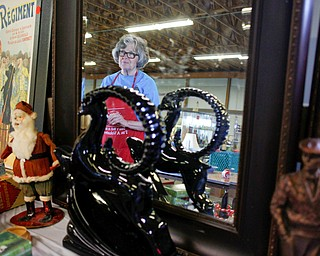 Mickey Cope Weaver, of Salem, arranges antiques that will be for sale in the antique room at the Angels for Animals garage sale at the Canfield Fairgrounds on Tuesday morning. The garage sale will take place Friday through Sunday at the fairgrounds. EMILY MATTHEWS | THE VINDICATOR