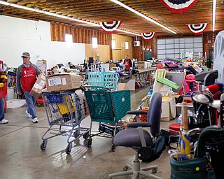 Volunteers Sonny Nabb, left, of Boardman, and Bill Varga, of Columbiana, arrange tools, sports equipment, and other outdoor items that will be for sale at the Angels for Animals garage sale at the Canfield Fairgrounds on Tuesday morning. The garage sale will take place Friday through Sunday at the fairgrounds. EMILY MATTHEWS | THE VINDICATOR