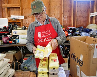 Volunteer Bill Varga, of Columbiana, arranges golf balls and other sports equipment that will be for sale at the Angels for Animals garage sale at the Canfield Fairgrounds on Tuesday morning. The garage sale will take place Friday through Sunday at the fairgrounds. EMILY MATTHEWS | THE VINDICATOR