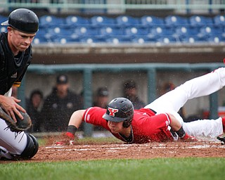 YSU's Lucas Nasonti slides safely into home before NKU's Collin Hohman gets a chance to tag him during their game at Eastwood Field on Friday. EMILY MATTHEWS   THE VINDICATOR