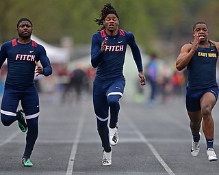AUSTINTOWN, OHIO - APRIL 20, 2019: (LtoR) Fitch's Ralph Fitzgerald and Isiah Tarver and East's Giovanni Washington run to the finish line during the boys 100 meter dash during the Mahoning County Track & Field Championship Meet at Austintown Fitch High School. DAVID DERMER | THE VINDICATOR