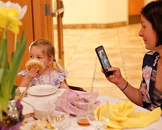 Beth Hawks, right, of Canfield, takes a photo of her daughter Claire Hawks, 2, as she eats a bagel at the annual Easter Brunch at Fellows Riverside Gardens on Sunday. EMILY MATTHEWS | THE VINDICATOR