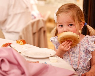 Claire Hawks, 2, of Canfield, eats a bagel at the annual Easter Brunch at Fellows Riverside Gardens on Sunday. EMILY MATTHEWS | THE VINDICATOR