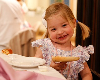Claire Hawks, 2, of Canfield, smiles as she eats a bagel at the annual Easter Brunch at Fellows Riverside Gardens on Sunday. EMILY MATTHEWS | THE VINDICATOR