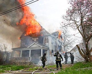 Firefighters work to put out a house fire on Wilson Avenue on Wednesday afternoon. EMILY MATTHEWS | THE VINDICATOR