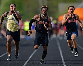 CORTLAND, OHIO - MAY 2, 2019: Howland's William Hines, center, races to the finish line against Michael Wilson and Harding's Michael Wilson during the boys 100 meter dash, Thursday afternoon during the Trumbull County Track Meet at Lakeview High School. DAVID DERMER | THE VINDICATOR