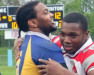 East's Turhan Henderson (5) and Chaney's Terrance Love hug after East defeated Chaney 45-12 at Rayen Stadium on Friday night.