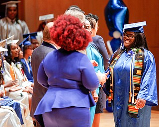 Jasmine Macklin shakes hands with staff members before receiving her diploma during the Youngstown Rayen Early College Class of 2019 commencement ceremony in DeYor's Ford Recital Hall on Friday. EMILY MATTHEWS | THE VINDICATOR