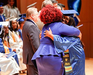 Jasmine Macklin hugs Monica James, the dean of Youngstown Rayen Early College, as she receives her diploma during the Youngstown Rayen Early College Class of 2019 commencement ceremony in DeYor's Ford Recital Hall on Friday. EMILY MATTHEWS | THE VINDICATOR