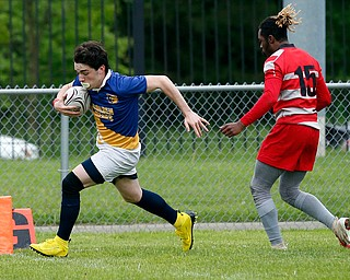 YOUNGSTOWN, OHIO - May 10, 2019: Rugby- Northwest Indians vs East Golden Bears.  East Golden Bears' Hunter Mathie (11, left) runs past Northwest Indians' Isaiah Grossnickle (15) for the score during the 1st half at Rayen Stadium. Photo by MICHAEL G. TAYLOR | THE VINDICATOR