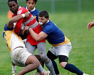 YOUNGSTOWN, OHIO - May 10, 2019: Rugby- Northwest Indians vs East Golden Bears.  East Golden Bears' Vincent Steele (15, left) and East Golden Bears' Samuel Cartagena (13, right) tackle Northwest Indians' Isaiah Grossnickle (15) during the 1st half at Rayen Stadium. Photo by MICHAEL G. TAYLOR | THE VINDICATOR