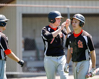 From left, Springfield's Clayton Nezbeth, Brannon Brungard, and Mitch Seymour celebrate after Brungard and Seymour score during the seventh inning of their game against South Range on Saturday at Springfield High School. Springfield won in the 10th inning 9-8. EMILY MATTHEWS | THE VINDICATOR