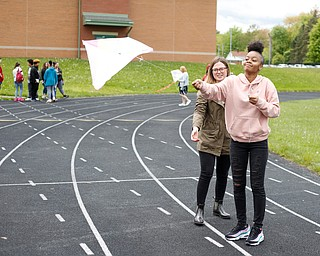 Hailey Black, left, a student teacher in Angela Dooley's 10th grade English class, helps Breasia Thomas, 14, a ninth grader at Chaney High School, fly a kite during a fundraiser for Save the Children, an organization that helps child refugees, on the track at Chaney High School on Tuesday afternoon. EMILY MATTHEWS | THE VINDICATOR