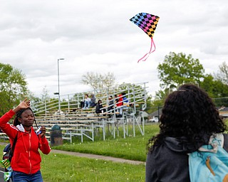 Alaja Johnson, left, 17, an 11th grader at Chaney High School, flies a kite while Nakaia McRae, 16, an 11th grader, watches during a fundraiser for Save the Children, an organization that helps child refugees, on the track at Chaney High School on Tuesday afternoon. EMILY MATTHEWS | THE VINDICATOR