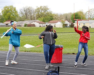 From left, Nevaeh Williams, 16, an 11th grader at Chaney High School, Nakaia McRae, 16, an 11th grader, and Alaja Johnson, 17, an 11th grader, dance as they fly kites during a fundraiser for Save the Children, an organization that helps child refugees, on the track at Chaney High School on Tuesday afternoon. EMILY MATTHEWS | THE VINDICATOR