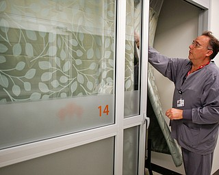 Mark Paczak, a registered nurse and the director of pain management in the new Southwoods Pain and Spine Center, shows how the fogged doors of patients' rooms and curtains provide patients with privacy on Monday morning. EMILY MATTHEWS | THE VINDICATOR