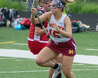 Mia Stana of Cardinal Mooney does her best to escape a Canfield defender in a Division II tournament game at Don Bucci Field on Thursday.