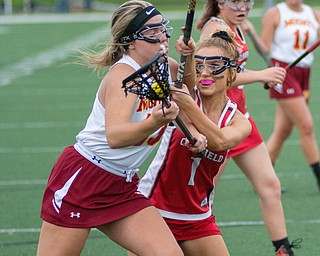 Grace Ramun (1) of Canfield attempts to keep Katie Enright of Cardinal Mooney from the cage in a Division II tournament game at Don Bucci Field on Thursday