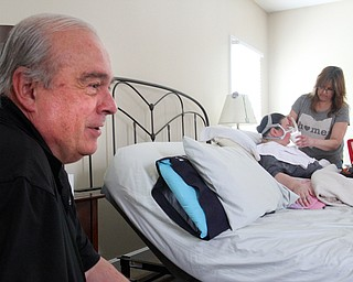 William D. Leiws The vindicator  Ron Moschella, Christine's father, looks on while a home healcare work helps Christine.