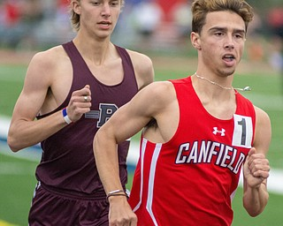 Giovanni Copploe of Canfield moves ahead of Mitchel Dunham of Boardman in the 1,600-meter run in the Division I District Track and Field Meet at Greenwood Chevrolet Falcon Stadium on Friday night..